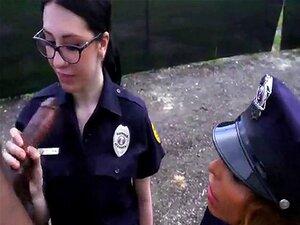 To kvinnelige politi kle en svart mann